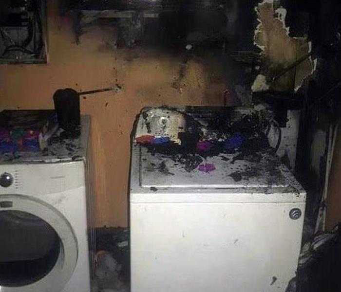 laundry room with washer and dryer covered in burned drywall and soot covered walls