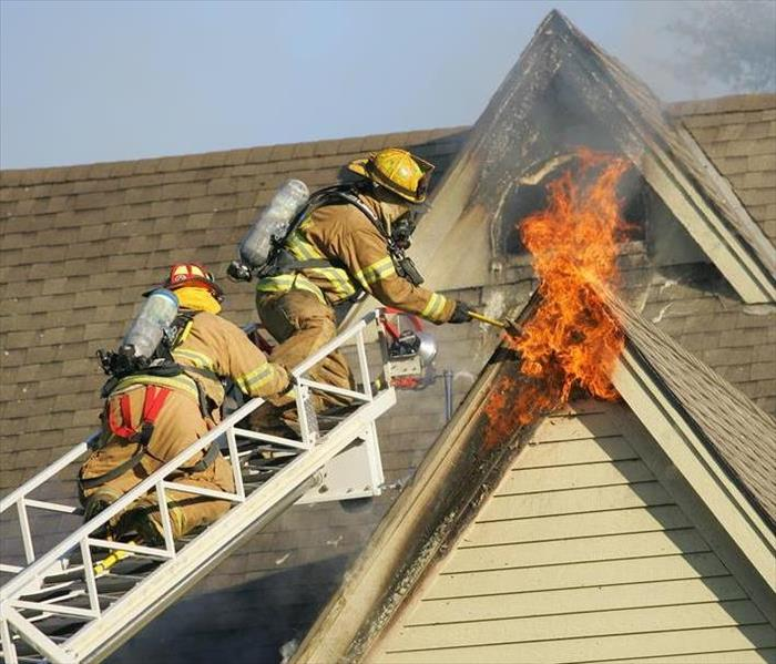 Two firefighters on a ladder trying to put out a fire in a second story window.