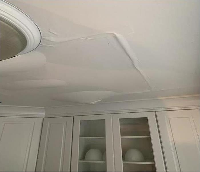 A ceiling in a home covered in water spots after a water damage disaster